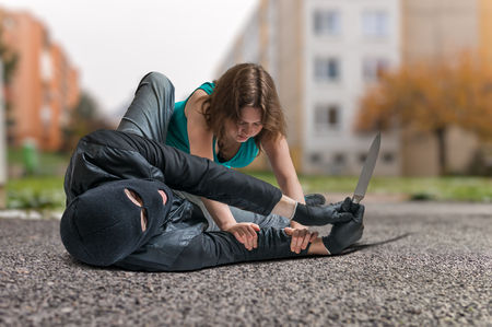 attacked: Young woman is fighting with armed thief with knife. Self defense concept.