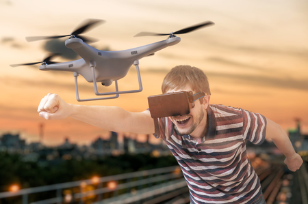 Man with 3D virtual reality glasses is controlling a flying drone.