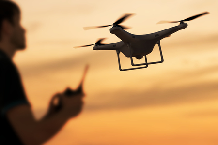 Man is controlling flying drone at sunset. 3D rendered illustration of drone.