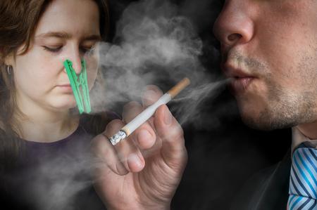 受動喫煙のコンセプトです。利己的な男はタバコを吸っています。女性では息もできない、彼女の鼻にペグ。 写真素材