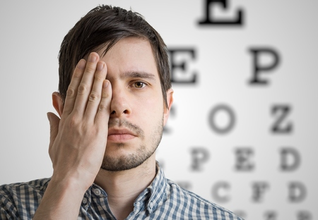 Young man is covering his face with hand and checking his vision. Chart for eye sight testing in background. Stock Photo