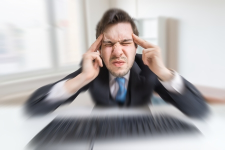Young overworked man is tired by working with compuiter and suffering from headache.