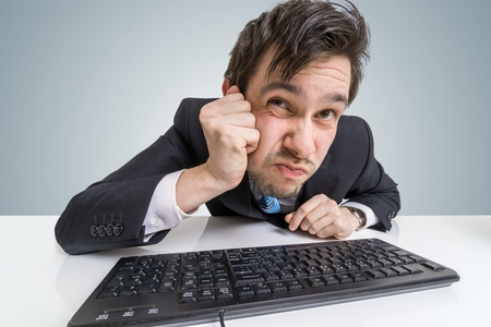 distrustful: Suspicious businessman is looking at screen at work. Stock Photo