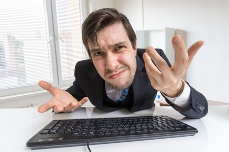 distrustful: Confused and unsure man is working with computer. Stock Photo