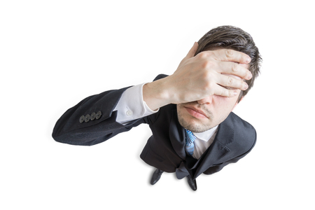 Young unhappy and stressed man made mistake and is covering his face with hand. Isolated on white background. View from top.