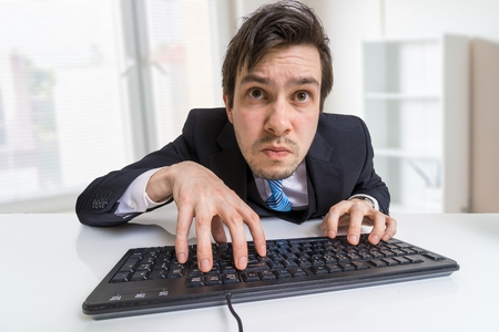 Young man is sitting behind table and working with computer. Stock Photo