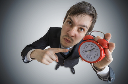 Angry manager is showing clock. Discipline concept. View from top. Archivio Fotografico