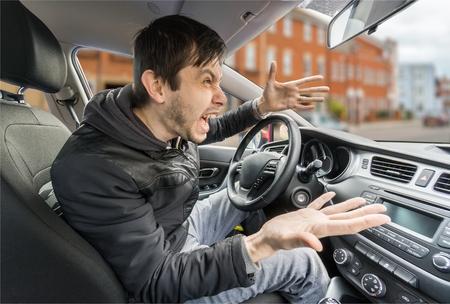 怒っている若いドライバーは車を運転して、叫んでいます。