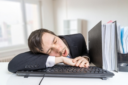 Tired overworked man is sleeping on keyboard in office at work.