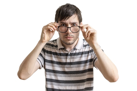 Serious man is putting on glasses. Isolated on white background. Stockfoto