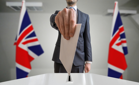 Election or referendum in Great Britain. Voter holds envelope in hand above ballot. United kingdom flags in background.