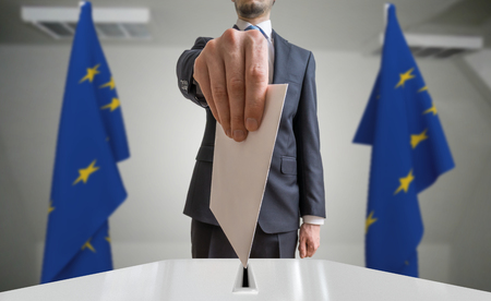 Election or referendum in European Union. Voter holds envelope in hand above ballot. EU flags in background.