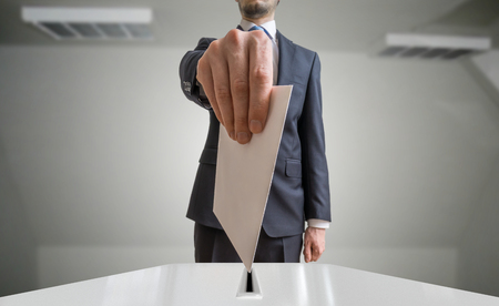 Election and democracy concept. Voter holds envelope or paper in hand above ballot. Stock Photo