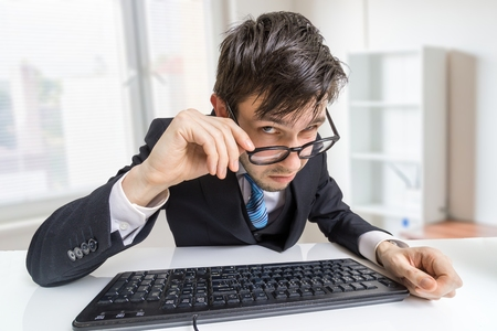 distrustful: Suspicious man in glasses is working in office and looking at you. Stock Photo