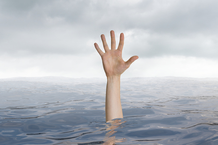 Man is drowning in ocean. Only hand is visible.