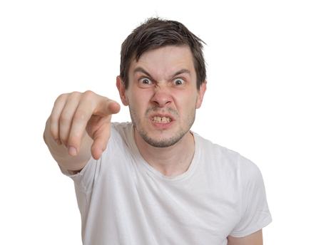 怒っている若い男はあなたの方に指しています。白い背景上に分離。