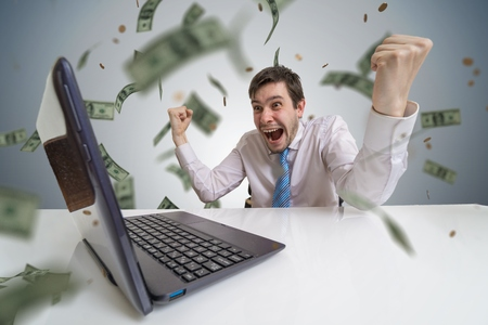 Young man wins a lottery online. Money are falling from above. Online betting concept.