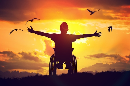 Disabled handicapped man has a hope. He is sitting on wheelchair and stretching hands at sunset.