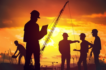 Silhouettes of workers working on construction site at suset.