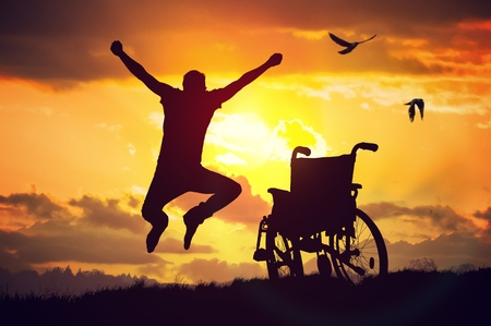 invalidity: A miracle happened. Disabled handicapped man is healthy again. He is happy and jumping at sunset. Stock Photo