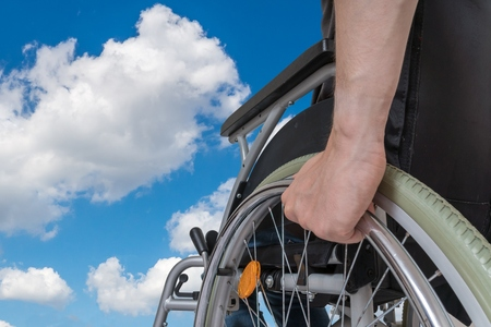 invalidity: Handicapped disabled man sitting on wheelchair against blue sky.