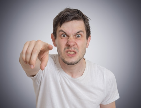 怒っている若い男はあなたの方に指しています。