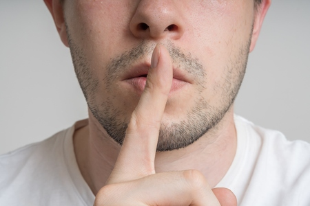Young man has finger on lips and showing be quiet gesture.