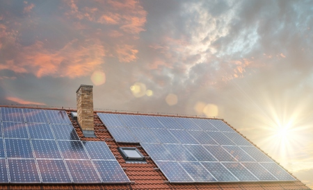 Photovoltaic or solar panels on roof at sunset.