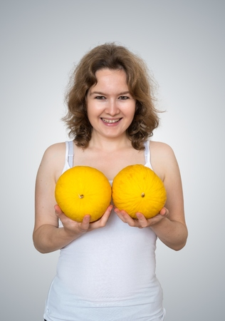 Young beautiful woman holds melons in hands above her breast. Plastic surgery and silicone implants concept. Stock Photo