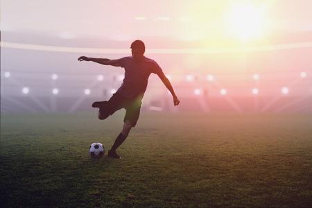 Joueur de football se bat un ballon dans le stade au coucher du soleil Banque d'images - 84313332