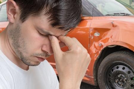 悲しい若者は車事故を起こした。バック グラウンドで破損した車。 写真素材 - 83992543