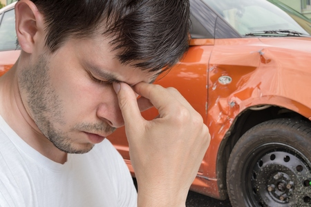 Young sad man had car accident. Damaged car in background.
