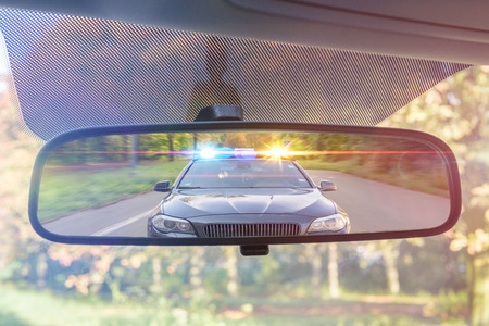 View on rear mirror of a car. Police car with lights and siren is chasing you. Stok Fotoğraf - 84080705