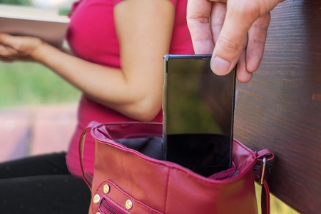 Pickpocket thief is stealing smartphone from bag of a woman reading book. Zdjęcie Seryjne - 84313266