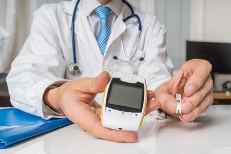 Doctor is giving glucometer to diabetic patient to measure blood sugar. Diabetes concept.