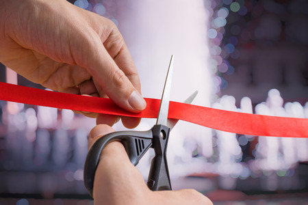 Man is cutting red tape or ribbon against defocused background. Opening ceremonial. Stockfoto