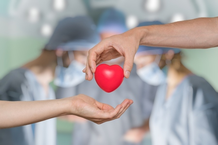 Organ donation concept. Hand is giving heart. Surgeons in background.