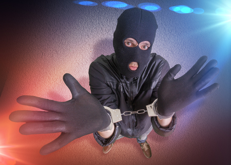 felonious: Thief or burglar with handcuffs is arrested. Police lights in background. View from above. Stock Photo