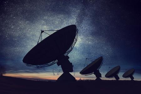 Sagome di antenne satellitari o antenne radio contro il cielo notturno. Osservatorio spaziale. Archivio Fotografico