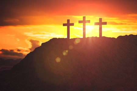 Silhouettes of three crosses at sunset on hill. Religion and christianity concept.