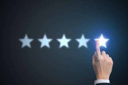 Ranking concept. Human hand is rating with 5 stars. Banco de Imagens