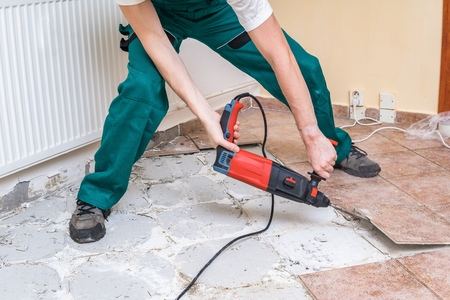 Renovation of old floor. Demolition of old tiles with jackhammer. Stock Photo