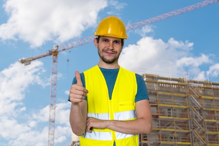 Happy worker in construction site is showing thumbs up gesture. Stock Photo