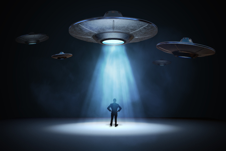 Alien invasion concept. Man standing under light beam from flying UFO spaceship. 3D rendered illustration.