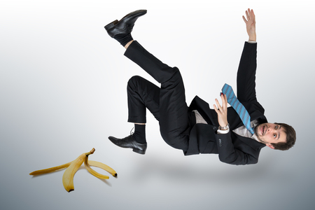 Businessman slipping on a banana peel. Фото со стока