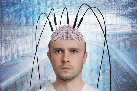 Neuroscience and brain research concept. Reconstruction of memory. Young man has cables and electrodes in his brain.