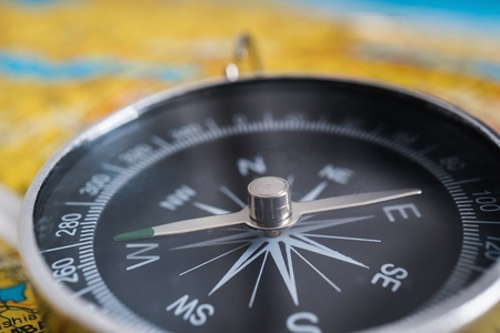 Close up view on compass and map in background.