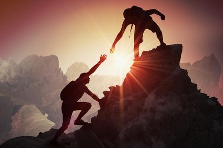 Hilfe und Hilfe-Konzept. Schattenbilder von zwei auf Berg kletternden und helfenden Leuten.