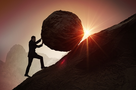 Sisyphus metaphore. Silhouette of businessman pushing heavy stone boulder up on hill. Stock Photo