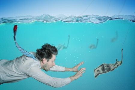 Greedy businessman is swimming in water and catching money on bait. Fraud concept. Stock Photo